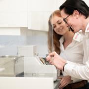 Optiker schleift ein Brillenglas an der Schleifmaschine