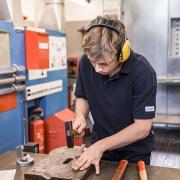VERBUND-Lehrling beim Hämmern in der Werkstatt